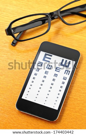 Eyechart on mobile with glasses - stock photo