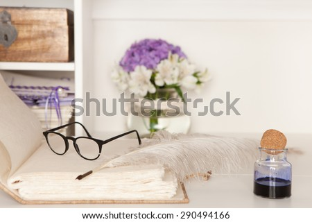 Eyeglasses and fountain pen on a blank page of a hand-bound book - stock photo