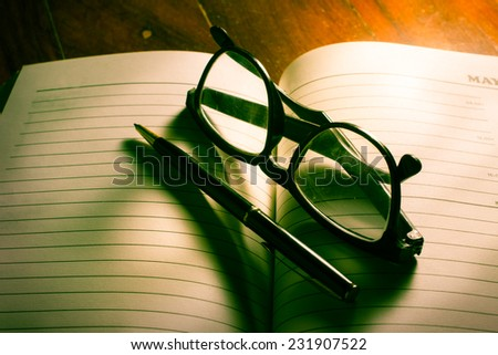 Eyeglasses and pen on plan book. - stock photo