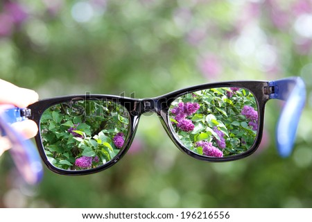 eyeglasses in the hand over blurred background - stock photo