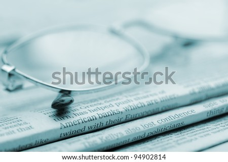 Eyeglasses lie on a pile of newspapers.Blue toned. A photo close up. Selective focus - stock photo