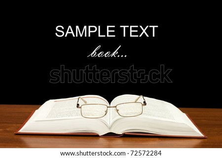 Eyeglasses on books on a wooden table - stock photo