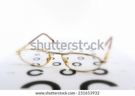 Eyeglasses on the ophthalmologic scale, shallow DOF. - stock photo