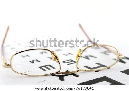 Eyeglasses on the ophthalmologic scale. Shallow DOF. - stock photo