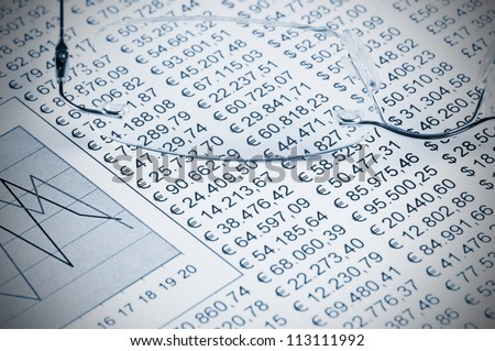 Eyeglasses on top of a sheet of paper white a chart and numbers - stock photo