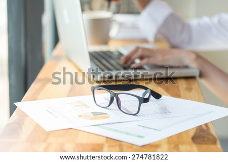 eyeglasses on wooden table with laptop - stock photo