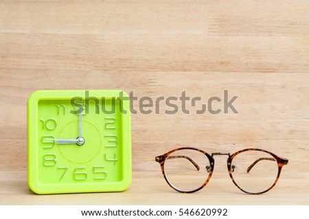 Eyeglasses with green clock on wooden table.