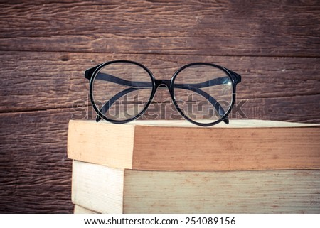 Eyeglasses with old book on wood table. - stock photo