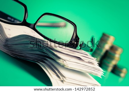 Eyeglasses with pile of bills and coins on green background - stock photo