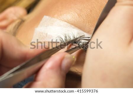 Eyelash extension procedure in beauty salon. Tweezers in hands of technician - stock photo