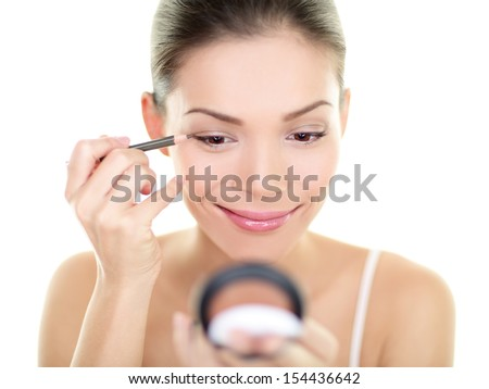 Eyeliner eye makeup beauty care woman. Asian girl putting eye pencil color on eyes looking in a pocket mirror smiling happy isolated on white background. Make up with multiracial Asian Caucasian girl. - stock photo