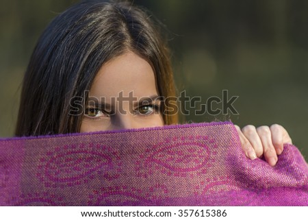 Eyes above the purple scarf. Pretty teenager girl with brown eyes is covering her face with the purple scarf in the afternoon woods. Shallow depth of field. - stock photo