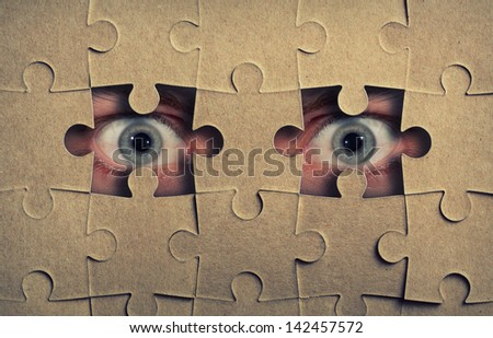 Eyes look out from the holes in jigsaw puzzle - stock photo