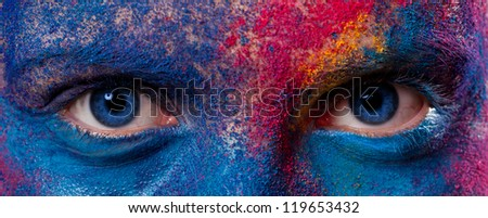 Eyes of woman with unusual paint make-up on black background - stock photo