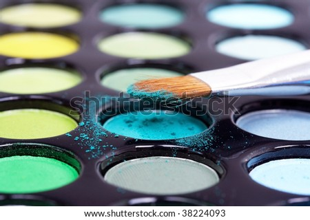 Eyeshadows with professional make-up brush on blue pattern