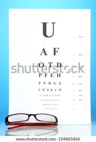 Eyesight test chart with glasses on blue background close-up - stock photo
