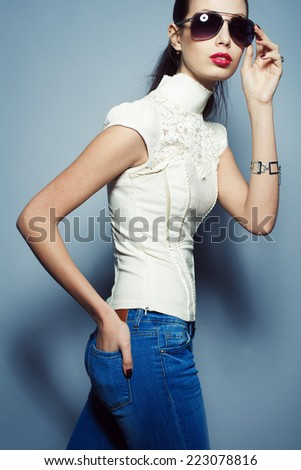 Eyewear concept. Fashionable beautiful young woman in trendy clothing (white waistcoat, blue jeans), sunglasses over blue background. Silver accessories. Horsetail hairdo. Hipster style. Studio shot - stock photo