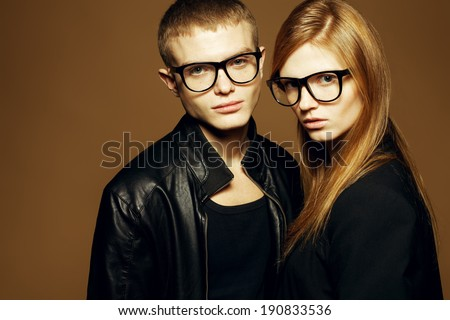 Eyewear concept. Portrait of gorgeous blond fashion twins in black clothes wearing trendy glasses & posing over golden background together. Perfect skin. Vogue style. Copy-space. Studio shot - stock photo