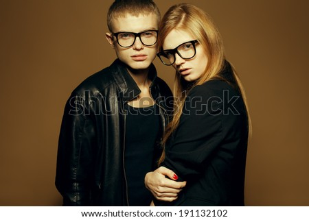 Eyewear concept. Portrait of gorgeous blond fashion twins in black clothes wearing trendy glasses & posing over brown (mustard) background together. Perfect skin. Vogue style. Copy-space. Studio shot