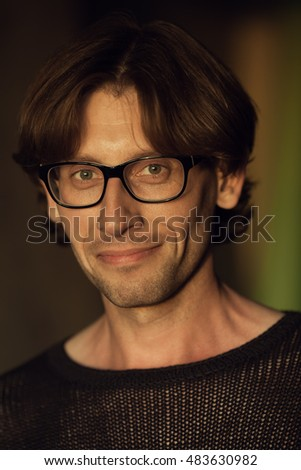 Eyewear concept. Portrait of gorgeous fashionable brunet in black sweater wearing trendy glasses and posing over brown background. Perfect skin. Vogue style. Close up. Studio shot