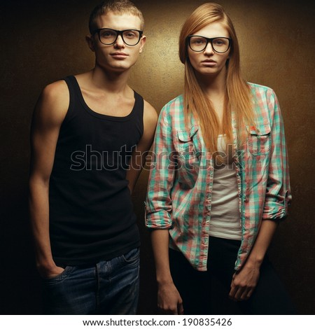 Eyewear concept. Portrait of gorgeous red-haired (ginger) fashion twins in casual shirts wearing trendy glasses and posing over golden background together. Hipster style. Studio shot - stock photo