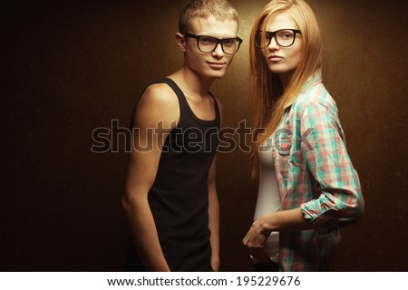 Eyewear concept. Portrait of smiling gorgeous red-haired (ginger) fashion twins in casual shirts wearing trendy glasses and posing over golden background. Hipster style. Copy-space. Studio shot - stock photo