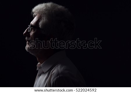Eyewear concept. Profile portrait of 60-year-old man standing over black background. Close up. Classic style. Copy-space. Studio shot