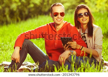Eyewear concept. Young couple in love having fun in the autumn park, sitting together and using tablet. Trendy casual clothing and stylish sunglasses. Perfect make-up & white shiny smile. Outdoor shot - stock photo