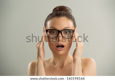 Eyewear glasses woman closeup portrait. Woman wearing glasses holding frame in close-up and looking surprised. Beautiful young caucasian female model on gray background. - stock photo