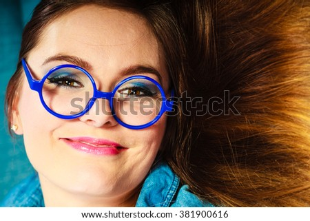 Eyewear. Young attractive woman face in blue glasses, closeup - stock photo