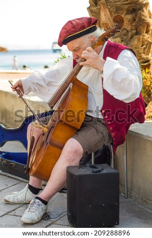 Eylat , Israel - October 28 , 2013:Street musician playing the cello on the waterfront of Eilat, Israel. Busker dressed in vintage clothing. - stock photo