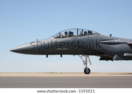 F-15 Strike Eagle taxiing to runway, closeup of cockpit with pilot and acknowledgement from the weapons systems officer - stock photo