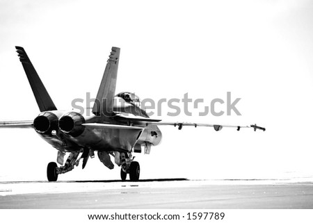 F18 taxiing to runway for takeoff. converted to b&w with overexposed background, focus on rear of aircraft.