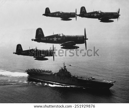 F4U's (Corsairs) returning from a combat mission over North Korea to the USS Boxer. Planes in the next strike are about to be launched from the carrier flight deck. Sept. 4, 1951. Korean War. - stock photo