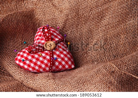 Fabric heart with color pins on sackcloth background - stock photo