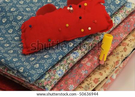 Fabric, pincushion, and chalk - stock photo