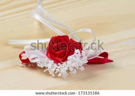 Fabric red rose with white decoration on the table - stock photo