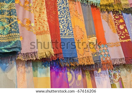 Fabrics and scarves for sale at a market stall - stock photo