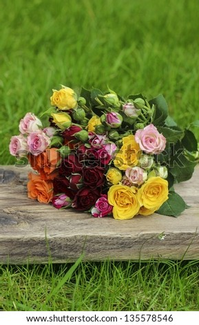 Fabulous bouquet of colorful roses on wooden tray in fresh spring garden - stock photo