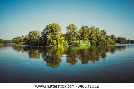 Fabulous reflection river island in serene surface of the water. Ukraine, the Dnieper river, vicinities of Kremenchuk - stock photo