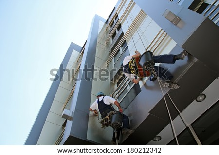 Facade Cleaning. Glass Cleaning Services.  Workers washing the windows facade of a modern office building. - stock photo