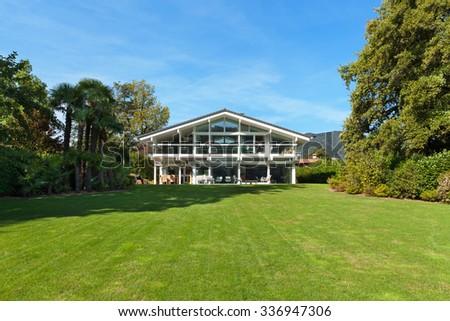Facade of a beautiful house with green garden, summer day  - stock photo