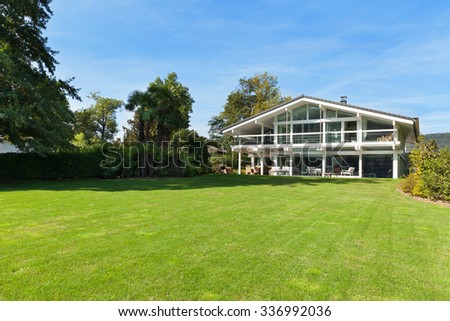 Facade of a beautiful house with green garden, summer day