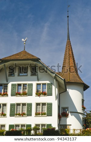 Facade of a Swiss house with green shutters and a circular tower topped with a spire - stock photo