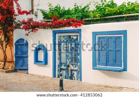 Facade of a very small white house with blue windows in Halkidiki, Greece - stock photo