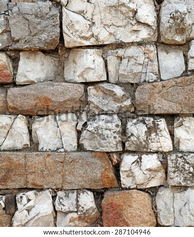 Facade of a weathered granite stone wall, for textural background. - stock photo