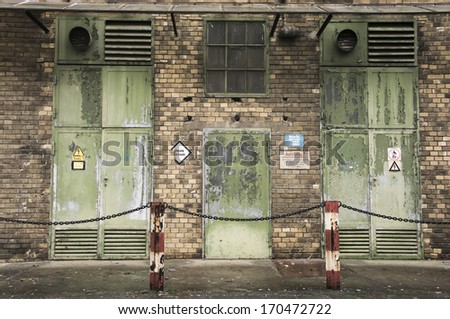 Facade of an industrial building from late 19th/early 20th century, unused and decayed. With some German signs. - stock photo