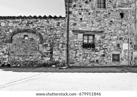 Facade of Italian house with closed window decorated with fresh flowers. Italian house exterior decorated with flowerpots  in a small Tuscany town. Black and white picture