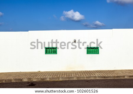 facade of mediterranean house with closed shutterblinds at midday - stock photo