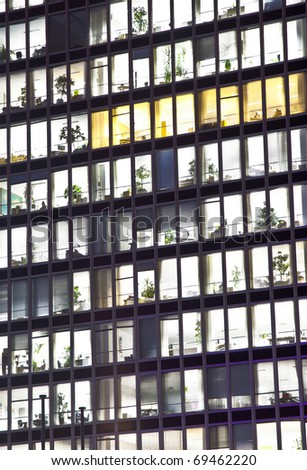facade of office building by night with illuminated windows - stock photo